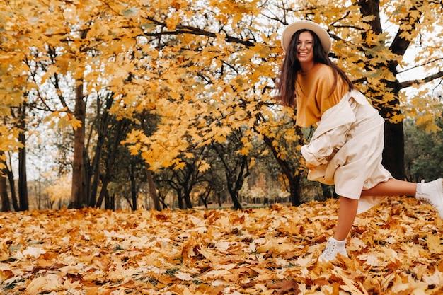 白衣と帽子をかぶった陽気な女の子が秋の公園で微笑む。黄金の秋の笑顔の女性の肖像画。
