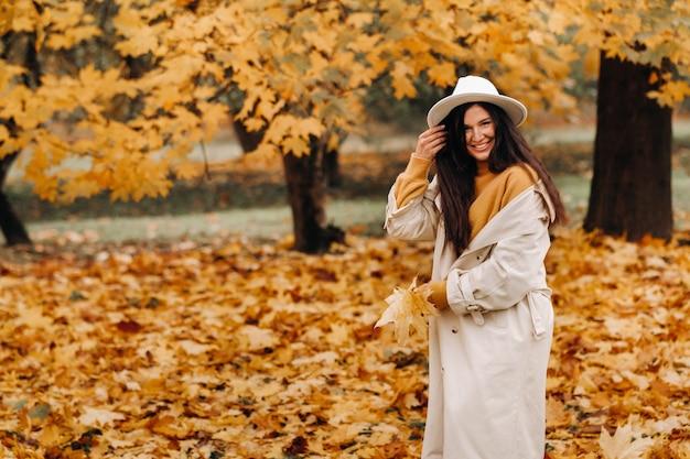白衣と帽子をかぶった陽気な女の子が秋の公園で微笑む