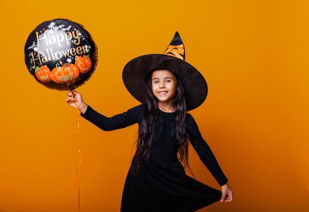 Веселая девушка в костюме ведьмы держит воздушный шарик с надписью halloween. концепция хэллоуина.