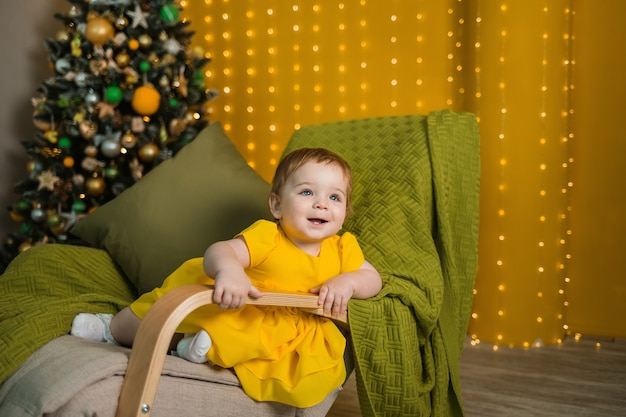 黄色いドレスを着た陽気な女の子がクリスマスツリーとロッキングチェアに座っています