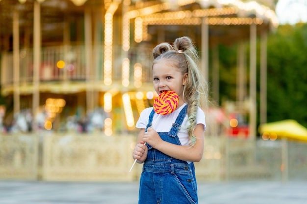 カルーセルの背景にある遊園地の陽気な女の子が大きなロリポップを食べる
