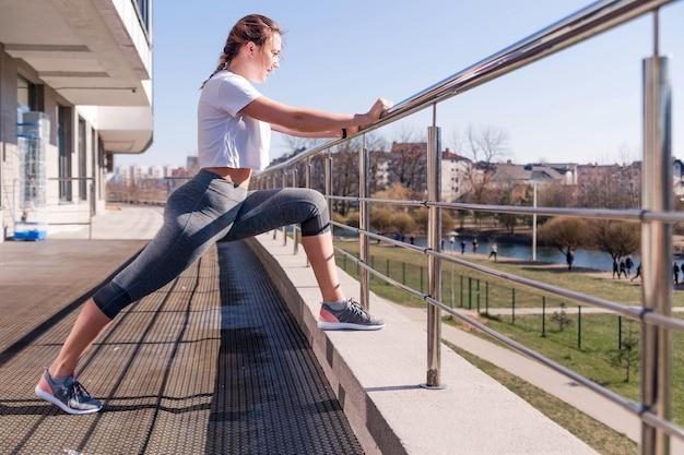 Веселой девушке подойдет утренняя пробежка. молодая женщина в белой футболке и серых леггинсах, опираясь на перила и вытягивая ноги и лодыжки. концепция разминки