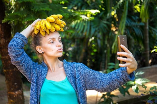 Веселая девушка делает селфи с бананами на голове