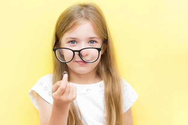 眼鏡をかけ、コンタクトレンズを保持している黄色の背景に陽気な女の子。学童の視力問題の概念。
