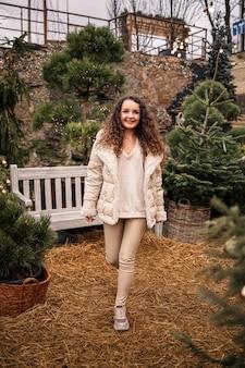 Веселая девочка гуляет среди деревьев и улыбается, у нее новогоднее настроение