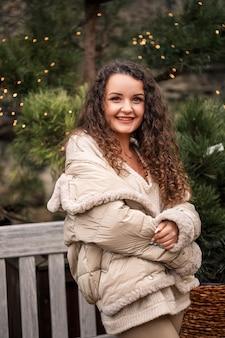 쾌활한 소녀는 나무 사이를 걷고 미소를 지으며 새해 분위기를 풍깁니다.