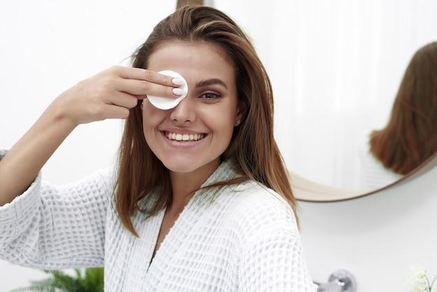 Веселая девушка с белоснежной улыбкой держит ватный диск возле глаз и смеется. милая брюнетка очищает кожу ватным диском с мицеллярной водой или очищающим средством.