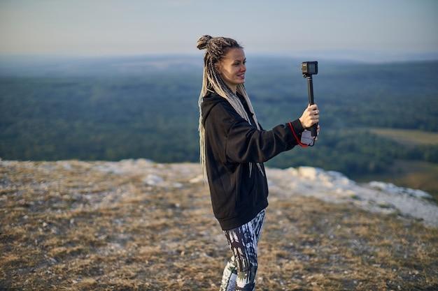 Веселая девушка с дредами в черной куртке снимает блог на камеру, стоя на вершине горы ...
