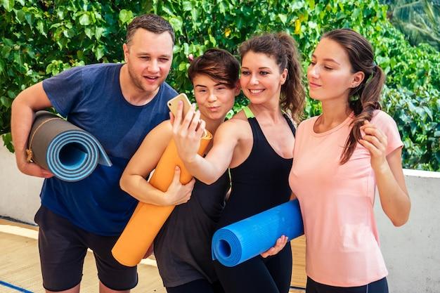 陽気な人々のグループは、ヨガのクラスでストレッチ体操をした後、電話で撮影されます