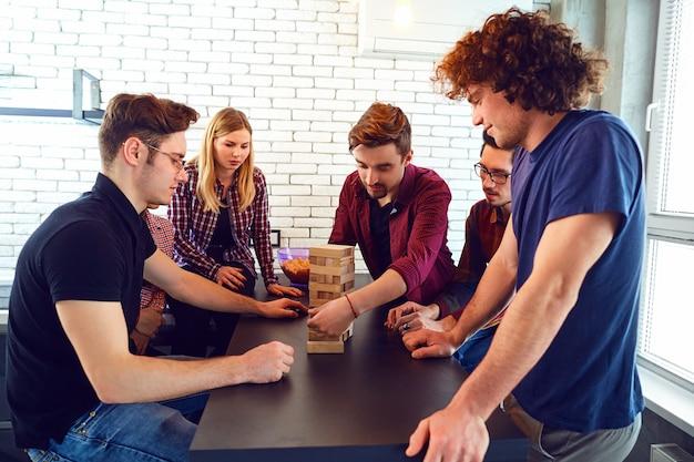 쾌활한 젊은 그룹이 방에서 보드 게임을합니다.