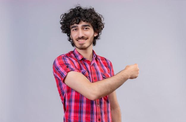 Веселый красавец с вьющимися волосами в клетчатой рубашке показывает
