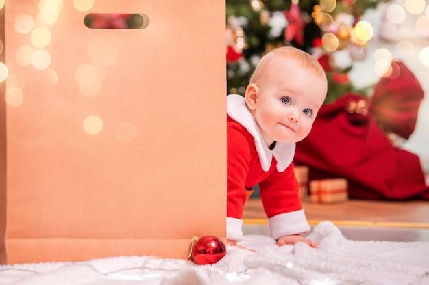サンタクロースの衣装を着た陽気な子供が、クリスマスツリーの背景にある大きなクラフトバッグの後ろからプレゼントを探しています。