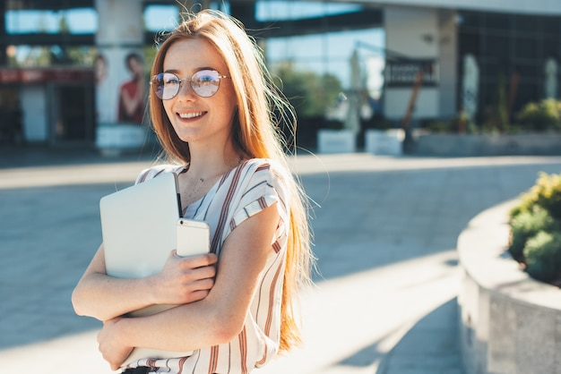 햇살 아래 야외에서 자유 시간을 걷고있는 매력적인 미소의 쾌활한 여성.