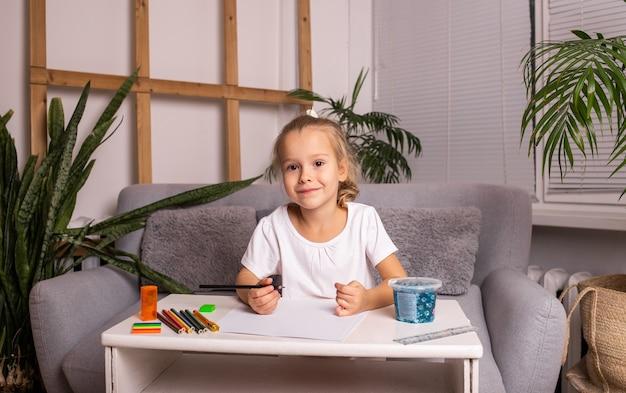 陽気な小さなブロンドの女の子がテーブルに座って、紙に鉛筆で描いています
