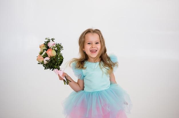 Веселая маленькая девочка в праздничном платье держит букет живых цветов на белом фоне с местом для текста
