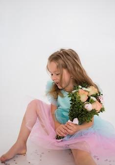 Веселая маленькая девочка в праздничном платье держит букет живых цветов на белом фоне