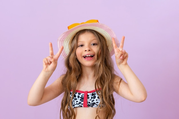 수영복을 입은 쾌활한 소녀가 손에 두 개의 손가락을 보여줍니다.