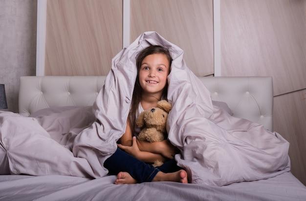 パジャマ姿の陽気な女の子がテディベアと一緒にベッドの毛布の下に座っています