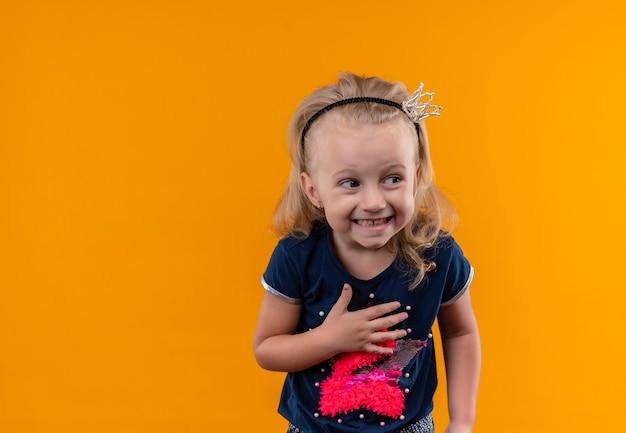 Веселая маленькая девочка в темно-синей рубашке в головной повязке с короной улыбается, глядя сбоку на оранжевую стену