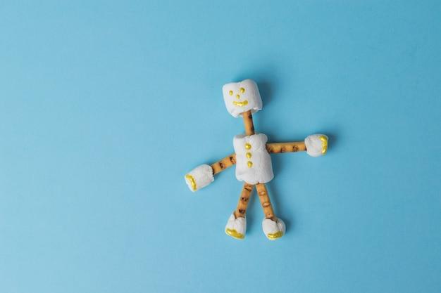 青い背景のマシュマロからの陽気な小さな男。お菓子のコラージュ。フラットレイ。