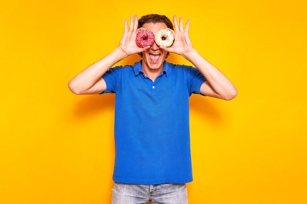 黄色の孤立した背景の陽気な男は、眼鏡のように彼の目の前にドーナツを保持します