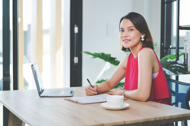 쾌활한 중년 아시아 여성 사업가는 편안한 캐주얼 복장으로 집에서 일하고, 컴퓨터 노트북에서 이메일을 확인하고, 재무 회계 문서 용지에 글을 쓰고 있습니다. 스톡 사진