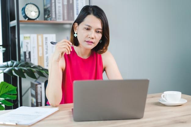 편안한 캐주얼 복장을 한 쾌활한 중년 아시아 여성 사업가가 집에서 일하고, 컴퓨터 노트북으로 이메일을 확인하고, 재무 회계 문서 용지에 글을 쓰고 있습니다. 비즈니스 스톡 사진