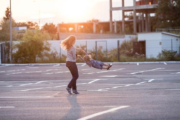陽気な母親が太陽の光を背景に小さな娘を回転させています