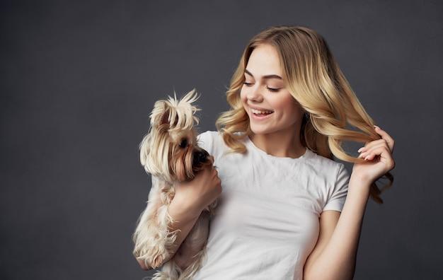 Веселая симпатичная женщина в белой футболке держит в руке маленькую собачку.