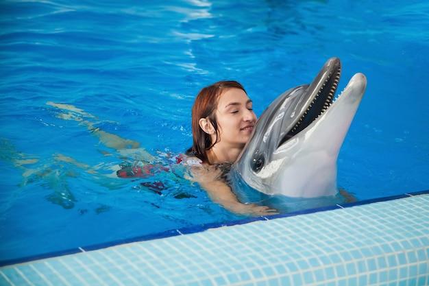 赤い水着姿の陽気な赤毛の女性が笑い、入浴し、イルカを抱きしめます