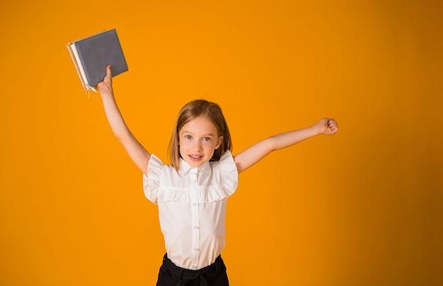 교복을 입은 쾌활한 여학생이 노란색 배경에 파란색 공책과 공간 사본을 들고 서 있습니다. 학교로 돌아가다