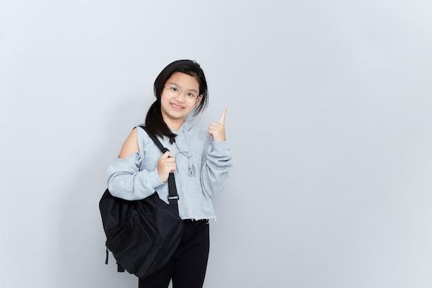 밝은 미소 아시아 소녀는 학교 가방을 착용