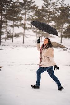 Веселая женщина, одетая в пальто, идет по снегу с зонтиком