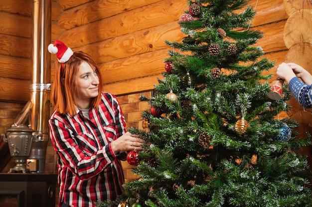 격자 무늬 셔츠를 입은 쾌활한 여자가 조명이 달린 벽난로의 배경에 크리스마스 트리에 아름다운 반짝 이는 공을 건다.