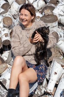 スタイリッシュな服を着た陽気な女性(花柄のドレス、ニットの手作り帽子とコート)は微笑んで、自然を楽しみ、白樺の丸太の山に猫を抱えています。村の生活のコンセプト