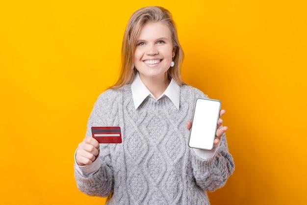 陽気な女性が携帯電話とクレジットカードからオンラインで買い物をしている