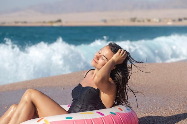 海沿いにドーナツ型の水泳サークルを持つ陽気な女性。休暇中のレジャーとエンターテイメントの概念。