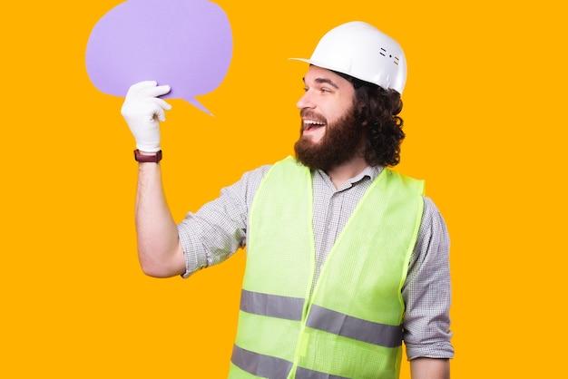 Веселый молодой бородатый архитектор смотрит на речевой пузырь, который он держит возле желтой стены, в шлеме, перчатках и люминесцентном жилете.