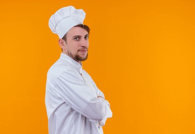 オレンジ色の壁を見ながら手を組んで白い制服を着た陽気な若いひげを生やしたシェフの男