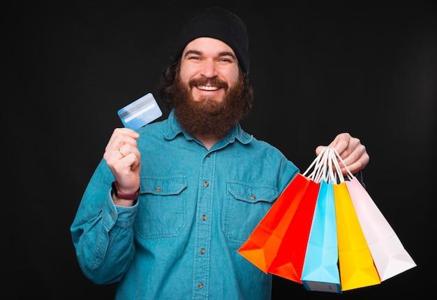 Веселый молодой бородатый мужчина смотрит и улыбается в камеру, держа в руках пакеты с покупками и кредитную карту, удовлетворяясь за продукты, которые он купил