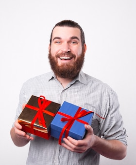 쾌활한 젊은 수염 난 남자가 흰 벽 근처에 두 개의 작은 선물을 들고 카메라에 행복을 찾고 있습니다
