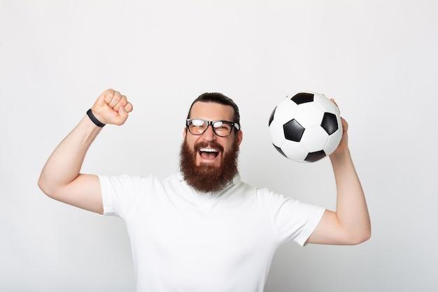 Веселый молодой бородатый мужчина, улыбаясь в камеру, держит футбольный мяч возле белой стены
