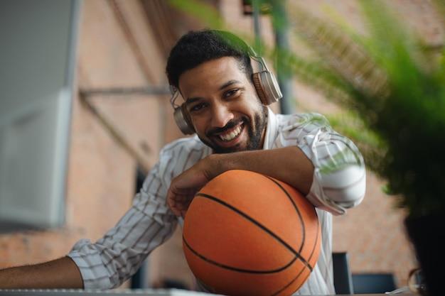 カメラを見ながら、オフィスで休憩しているヘッドフォンとボールを持つ陽気な青年実業家。