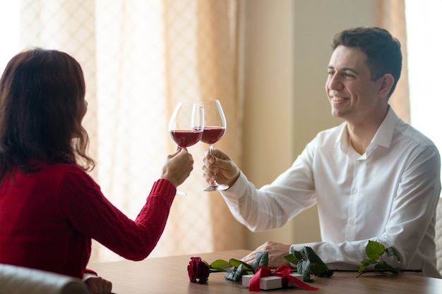 レストランでワイングラスを横切る陽気な若いカップル。カフェでワインを飲む男性と彼のガールフレンド。テーブルの上に赤いバラ。バレンタインデーのコンセプト。