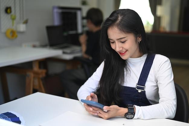 Веселая молодая самка сидит в офисе и с помощью смартфона.