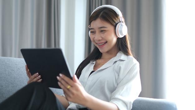 Веселая молодая женщина с наушниками использует планшет для просмотра онлайн-трансляции фильмов на диване в гостиной.