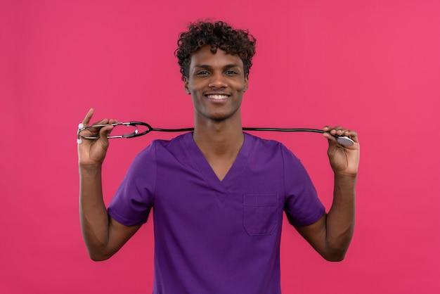 Веселый молодой красивый темнокожий доктор с вьющимися волосами в фиолетовой форме держит в руках стетоскоп