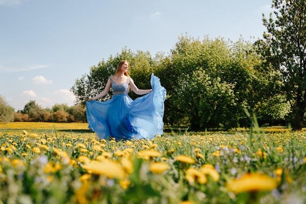 볼 가운 파란색 드레스를 입은 쾌활한 젊은 여성이 봄 알레르기가 없는 컨셉에 노란 민들레가 피어 들판을 가로질러 달리고 있습니다.