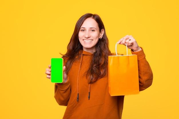 Веселая молодая женщина держит сумку для покупок и телефон