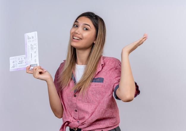 Веселая молодая женщина в красной рубашке держит билеты на самолет, глядя на белую стену